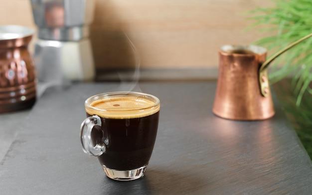 Koffiepauze. verse espresso stoom stijgt in een glazen beker boven de beker, selectieve focus. sterke aromatische koffie gebrouwen in een turk voor het ontbijt, het idee om koffie te maken op traditionele oosterse manier