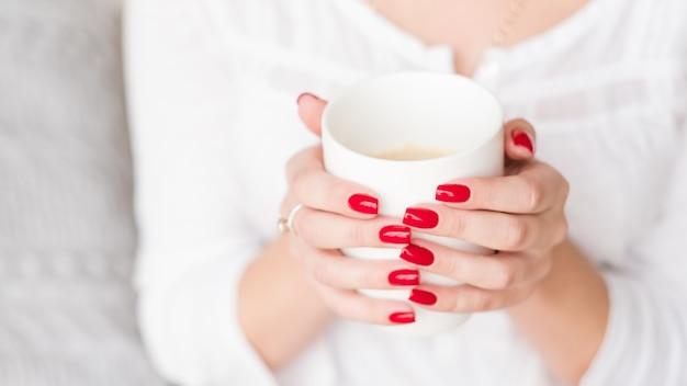 Koffiepauze. vrije tijd. vrouwenhanden met rode manicure houden witte kop latte.