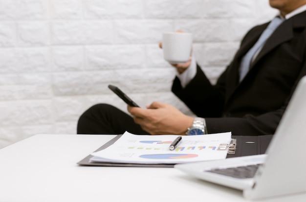 Koffiepauze zakenman uitvoerende werken ontspannen op laptop achter zijn bureau.