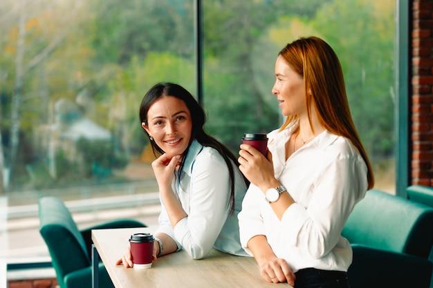 Koffiepauze. zakenvrouwen drinken koffie in een groot modern kantoor met grote ramen. ze wachten op het begin van de vergadering en nemen zakelijke beslissingen.