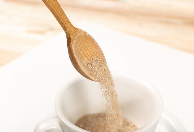 Koffiepoeder stroomt uit houten lepel