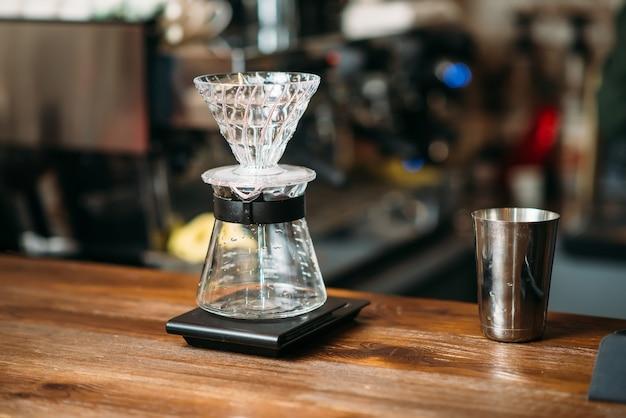 Koffiepot en metaalglas op een toog.