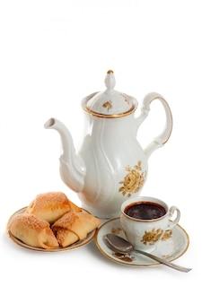 Koffiepot met kop en schotel van cakes