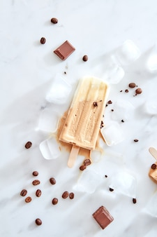 Koffiesorbet met koffiebonen en stukjes chocolade op een marmerijs
