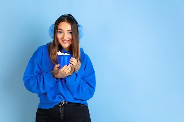 Koffietijd. blanke vrouw portret op blauwe ruimte. mooi vrouwelijk model in warme kleren