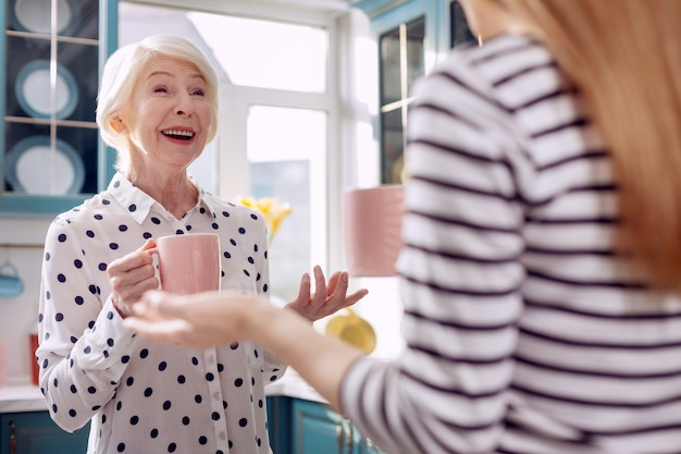 Koffietijd. de focus ligt op een schattige oudere vrouw die communiceert met haar jonge dochter in de keuken en aangenaam lacht terwijl ze koffie drinkt