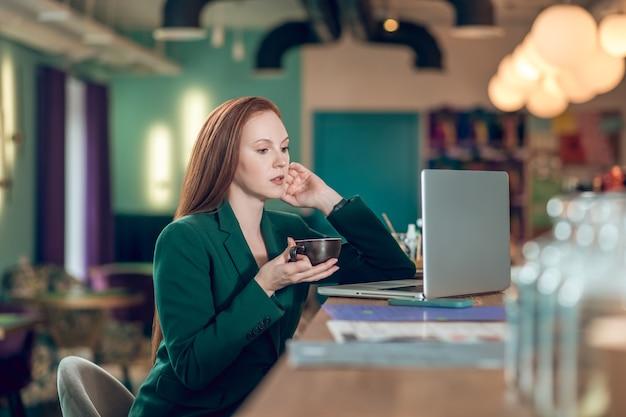 Koffietijd. jonge serieuze langharige vrouw in een groen zakelijk pak die koffie drinkt terwijl ze voor een laptop in café zit