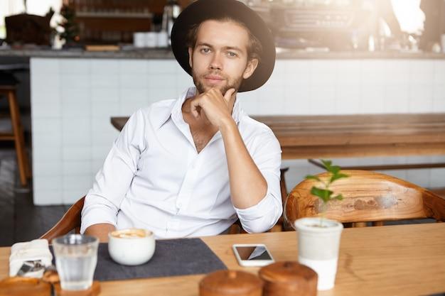 Koffietijd. modieuze jonge hipster in zwarte hoed rust in café, zittend aan tafel met kopje cappuccino en generieke mobiele telefoon, hand op zijn kin, kijken en glimlachen