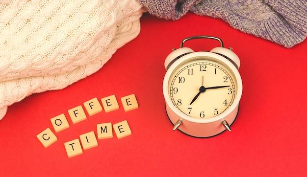Koffietijd ochtendconcept, oude vintage wekker op rode retro achtergrond, gebreide truien foto