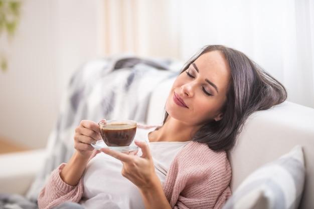 Koffietijd ontspannende vrouw op een bank in het huis.