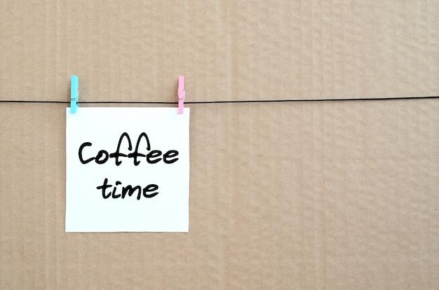 Koffietijd. opmerking staat op een witte sticker die met een wasknijper aan een touw op een achtergrond van bruin karton hangt