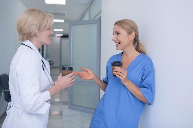 Koffietijd. twee glimlachende vrouwelijke artsen die zich in gang bevinden, koffie drinken