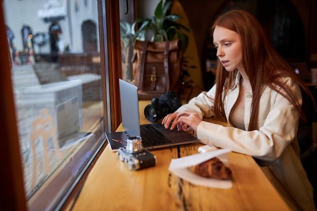 Koffietijd, zelfverzekerde vrouw die mobiele telefoon en laptop gebruikt in café, aan het werk