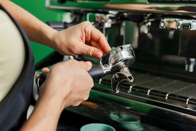 Koffiewinkelmedewerker die koffie op koffiemachine dichtbij voorbereidt