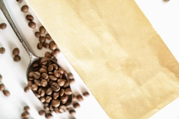 Koffiezak met koffiebonen op een zilveren lepel die op witte achtergrond wordt geïsoleerd