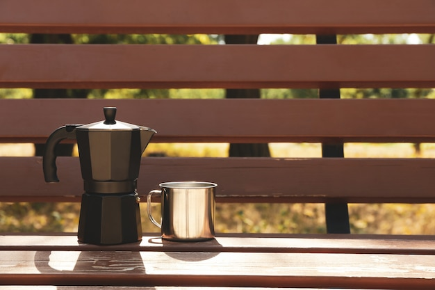 Koffiezetapparaat en metalen beker op bank buiten