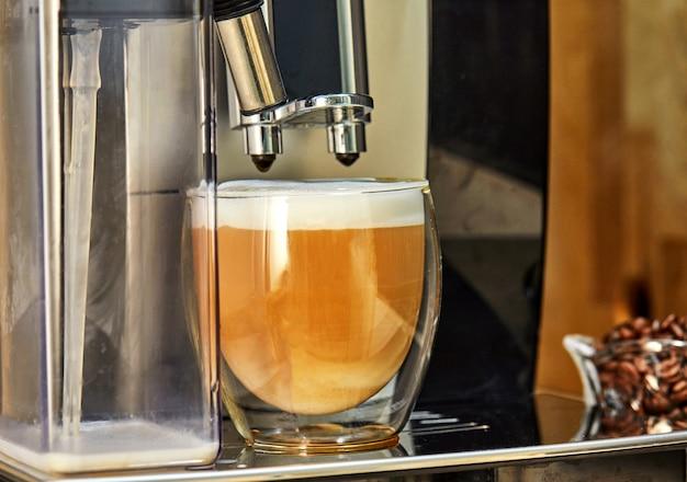 Koffiezetapparaat maakt cappuccino koffie in een transparante beker.
