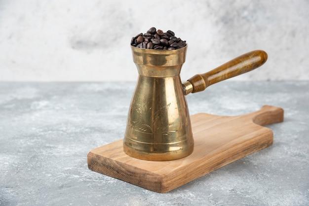 Koffiezetapparaat vol gebrande koffiebonen op een houten bord.