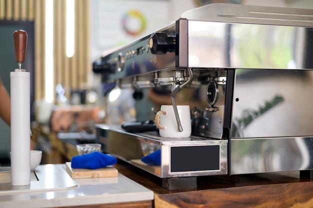 Koffiezetapparaat zwarte koffie maken en gieten in een kopje in café
