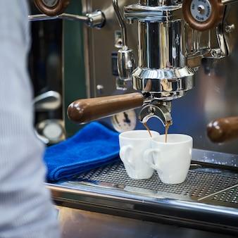 Koffiezetapparaatmachine die espresso in witte kop vult.