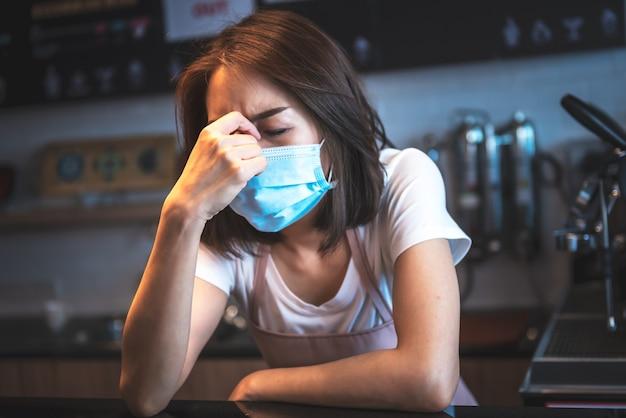 Koffiezetapparaatvrouw draag een chirurgisch masker ze is gestrest, overstuur vanwege de epidemische situatie van de covid-19