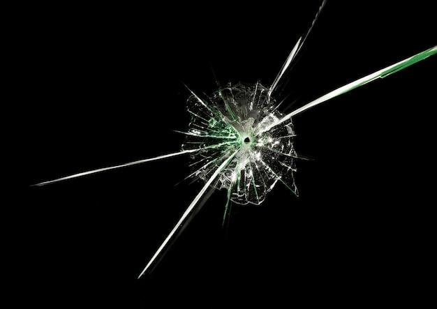 Kogelgat in glas met lange kruisende scheuren en groene weerspiegelingen op geïsoleerde zwarte