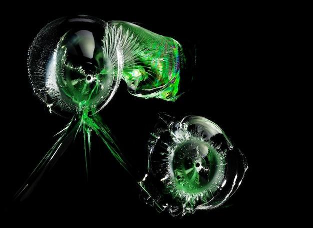 Kogelgaten met groene reflecties in glas op zwart. macro. zijaanzicht.