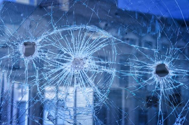 Kogels doorboorden het glas in het raam in de stadsstraat