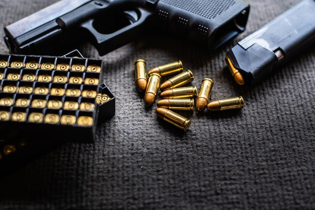 Kogels en pistool op zwart fluwelen bureau