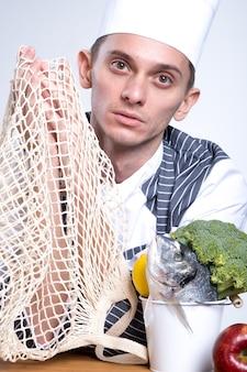 Kok chef-kok eco katoenen koordzak in handen houden. vis, citroen en broccolli in emmer op houten tafel met rode appel, herbruikbare netto netzak. ecologie concept