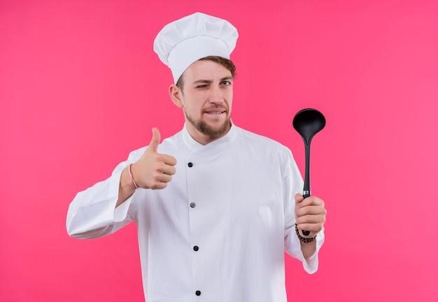 Kok die camera bekijkt die één oog sluit en als gebaar met lepel aan kant toont die zich over roze muur bevindt