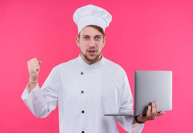 Kok die camera bekijkt, wint uitdrukking op gezicht met notitieboekje bij de hand over roze muur