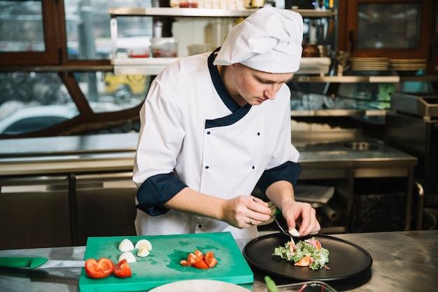 Kok die gekookt ei op plaat met salade zet