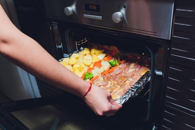 Kok die klaar gebraden gebakken kip met groenten uit de oven nemen. thuis koken concept.