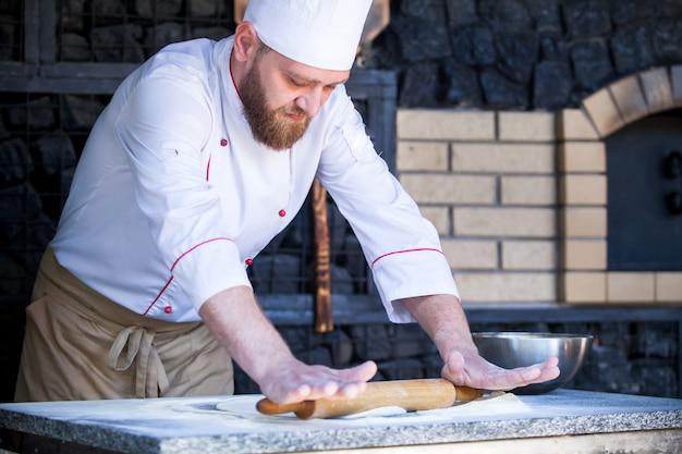 Kok die pizza in een restaurant voorbereidt.