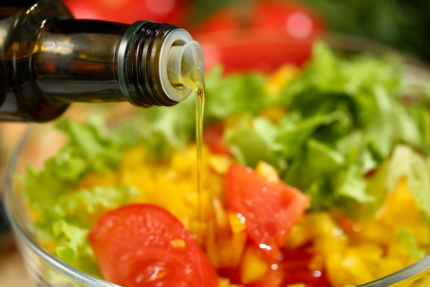 Kok houdt fles in de hand en druppelt olijf