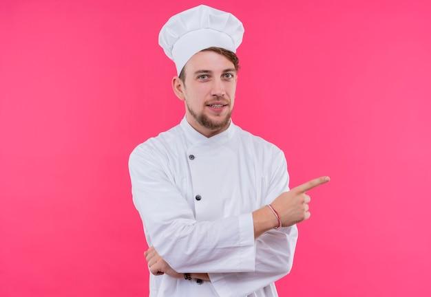 Kok kijkt naar cameraplezier op gezicht wijzend staande over roze muur