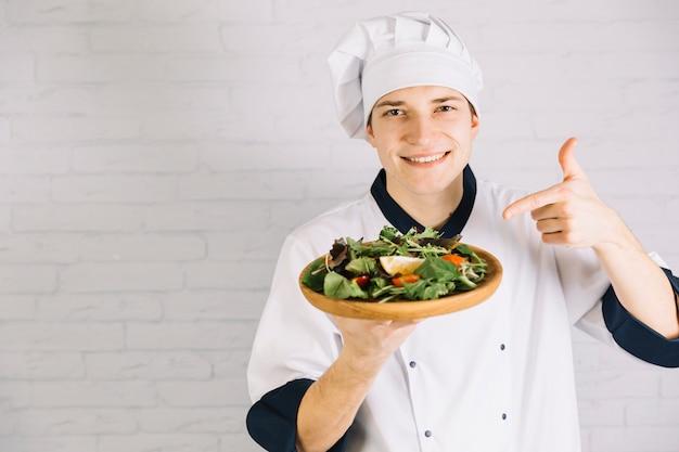 Kok wijzende vinger op salade op houten plaat