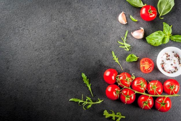 Koken, achtergrond. ingrediënten voor het koken. specerijen (zout peper) greens (rucola peterselie basilicum) en cocktail cherry tomaten op een zwarte stenen tafel. bovenaanzicht copyspace