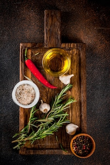 Koken achtergrond, kruiden, zout, specerijen, olijfolie op snijplank