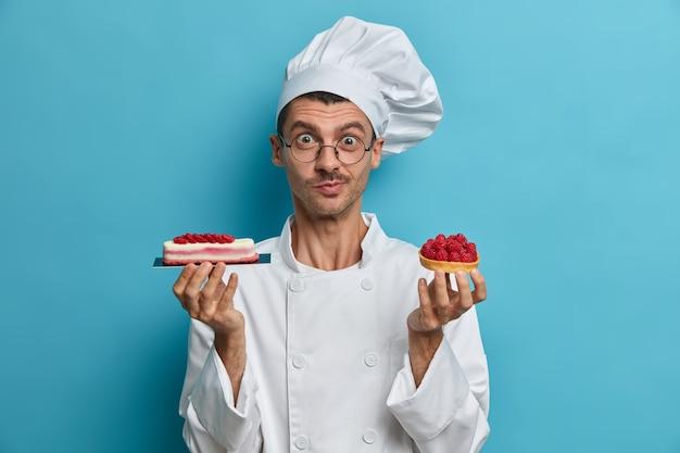 Koken, beroep, bakkerijconcept. jonge mannelijke fornuis bevat smakelijke zoetwaren, desserts versierd met bessen
