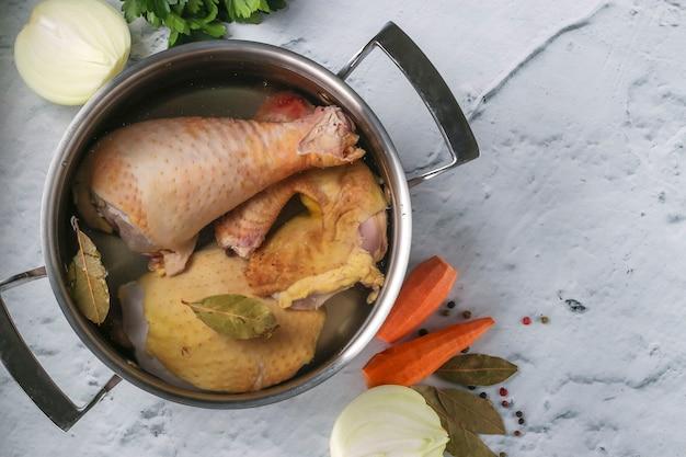 Koken bouillon van zelfgemaakte kip met peper en laurier in een pan op een marmeren achtergrond.
