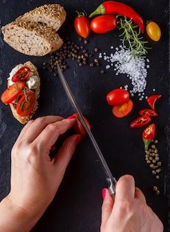Koken bruschetta. vrouwelijke handen slced tomaten