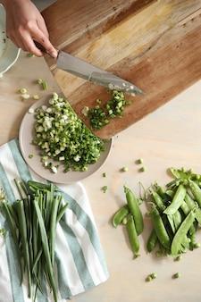 Koken. chef-kok snijdt greens in de keuken