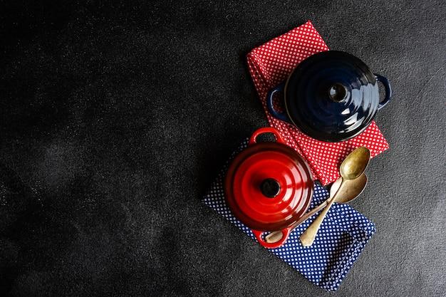 Koken concept met keramische potten en handdoeken op donker beton met kopie ruimte