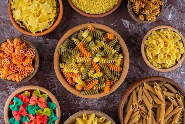 Koken concept met verschillende rauwe pasta op marmeren oppervlak.