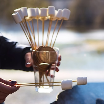 Koken dessert met marshmallows bij het vuur op een picknick in de natuur