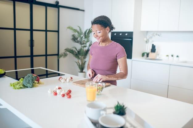 Koken. een vrouw met een donkere huid die in de keuken kookt en groenten snijdt