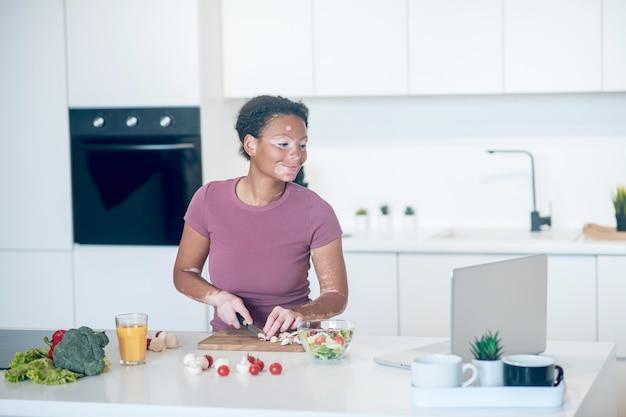 Koken. een vrouw met een donkere huidskleur kookt in de keuken terwijl ze een kookvlog kijkt