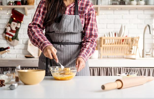 Koken en bakken. jonge latijns-vrouw zwaaien eieren koken in de keuken